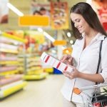Woman checking the nutrition content of an item at the grocery store