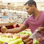 A man choosing among fresh fruits at a grocery store