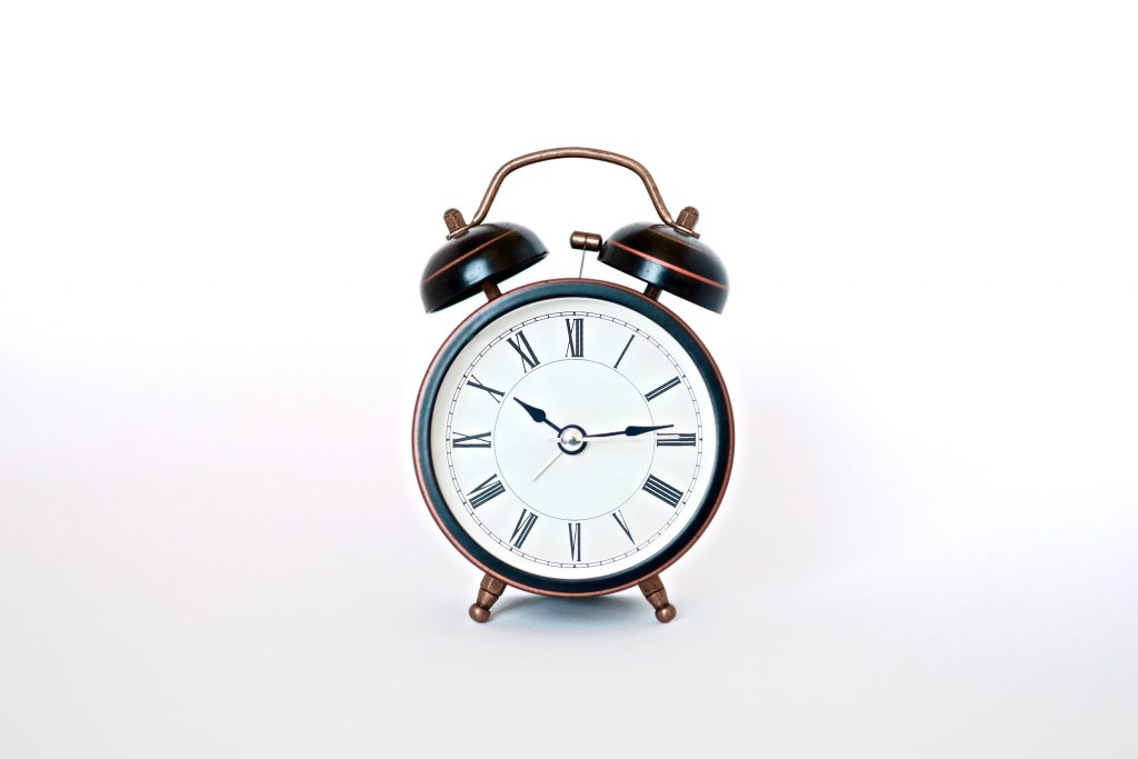 A black vintage alarm clock with bells and bronze accents